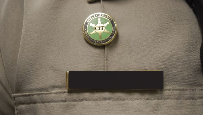 This image shows a Crisis Intervention Team pin on the uniform of a Shelby County Sheriff's deputy who was present at the fatal shooting of Nancy Jane Lewellyn in Lakeland on March 17, 2017. This was one of many photos taken during the shooting investigation. Though identifying information is redacted in this image, personnel records suggest that this is the uniform of Deputy Justin Jayroe, who is certified as a CIT member and did not fire his weapon.