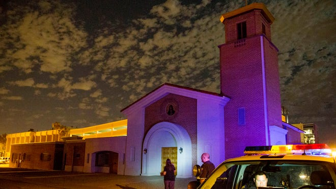 Phoenix Police officer Joseph Stussy, in center and Luis Orozco, in van, investigate at the Mother of Mercy Mission, where one priest was shot and killed and another wounded at a Catholic church Wednesday, June 11.