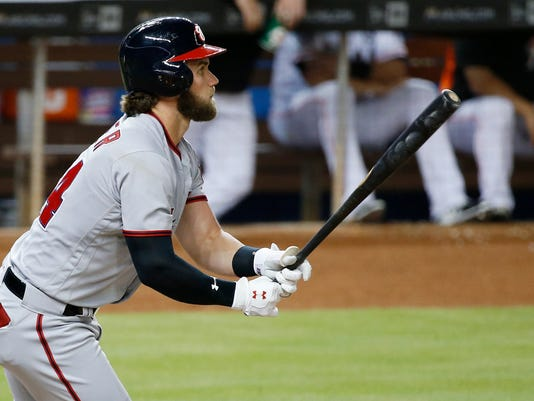 Washington Nationals' Bryce Harper watches his two-run single during the third inning of the team's baseball game against the Miami Marlins, Tuesday, June 20, 2017, in Miami. Harper extended his hitting streak to 13 games as the Nationals defeated the Marlins 12-3. (AP Photo/Wilfredo Lee)