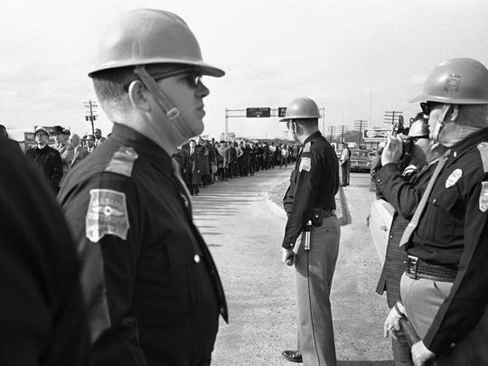 In this March 10, 1965 file photo, a long line of demonstrators approaches a contingent of state troopers who turned them back during a voters rights march at Selma, Ala. The group returned to a church with no incident.
