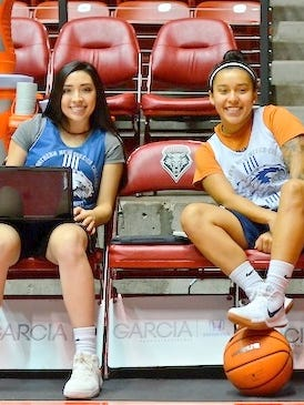 Leah Deaguero sits with Kyanne Kowatch, finishing homework between the shoot around and game with University of New Mexico Lobos.