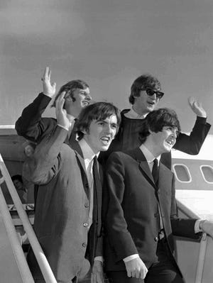 The Beatles wave after arriving at the San Francisco airport Aug. 18, 1964 to begin an American tour. Clockwise from top right; John Lennon, Paul McCartney, George Harrison and Ringo Starr.  (AP Photo)