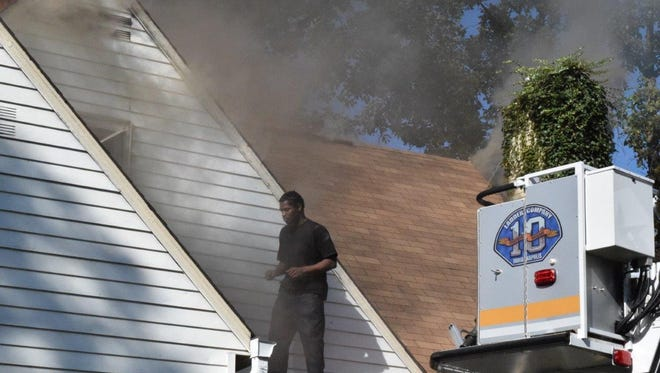 A man who police said set a Layman Avenue home on fire and refused to leave it is seen standing on the roof of the burning home Monday morning.