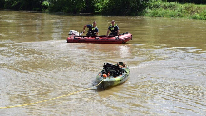 Indianapolis firefighters tow a kayak to shore after rescuing four men and five women from the White River on June 24.