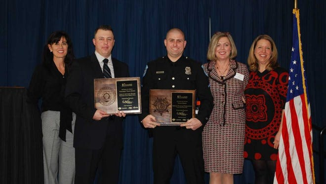 Officer First Class Nicholas Harrington (center right) of the Ocean View Police Department and Deputy First Class Anthony Rhode of Worcester County Sheriff's Office (center left) receive an award for valor from the Overall Bethany-Fenwick Area Chamber of Commerce and Carl M. Freeman Companies.