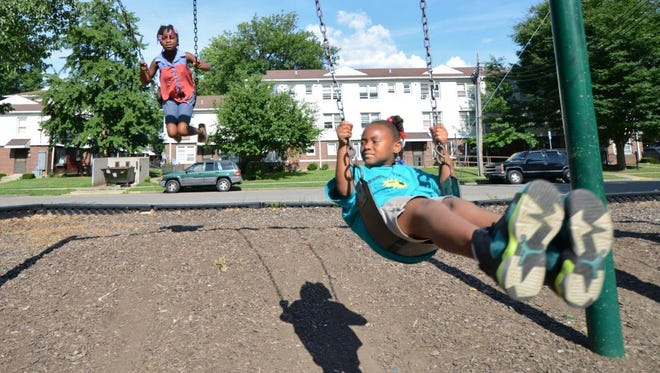 Demariyah Flint, 8; and Stevielynn Harris, 7, play on the swing set outside the Baxter Community Center at 12th and Jefferson streets, next to Beecher Terrace public housing development.