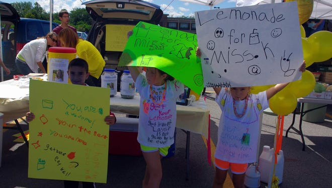 The kids made their own signs. (L-R) Luca Russo, Nora Bartosiewicz and Julia Santoli