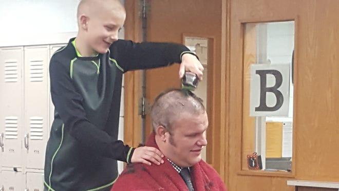 Jackson Johnston shaves the head of Pekin Middle School Principal Tim Hadley on Tuesday, Jan. 10, 2017.
