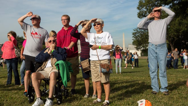 The family of Jan Bonacci, center, of Shelby Township  gathers on the West Front of the U.S. Capitol building to watch a telecast of Pope Francis addressing a joint session of U.S. Congress and to greet him as he makes an appearance on the West Front speaker's office balcony on Sept. 24, 2015.