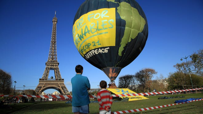 Boys look at a hot air balloon of the environmental group Greenpeace, near the Eiffel Tower ahead of the 2015 Paris Climate Conference, in Paris, Saturday, Nov. 28, 2015. The conference with more than 100 heads of state is scheduled to start on Nov.30.