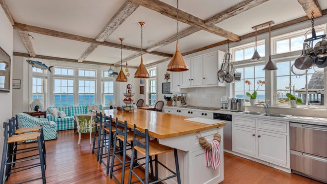 The custom kitchen features a spacious center island for meal prep and ocean views.