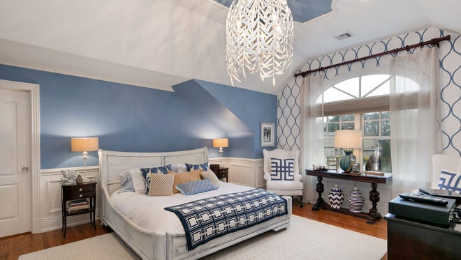 The master bedroom with hardwood flooring, a vaulted cathedral ceiling and tray details.