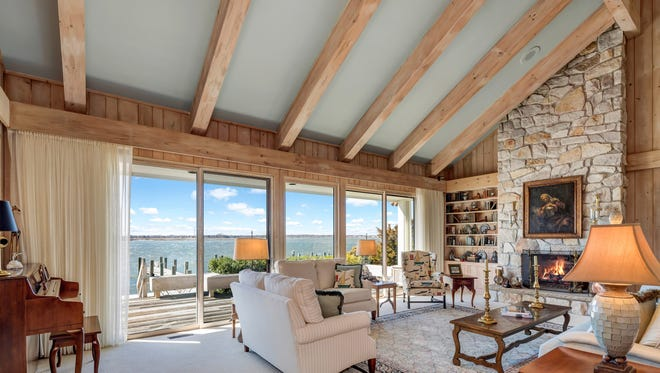 The living room comes with a beamed vaulted ceiling, a gas fireplace and sliding doors leading to the bay.