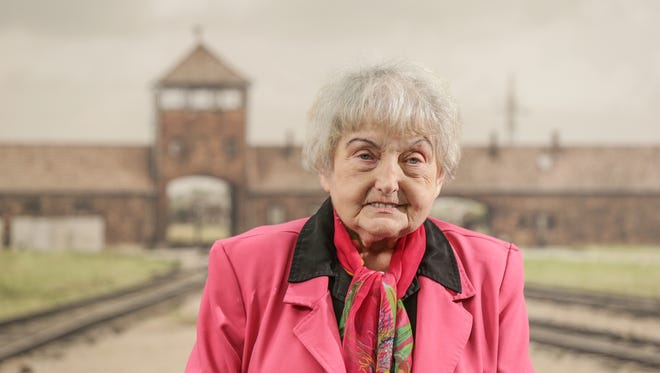 Holocaust survivor Eva Mozes Kor stand in front of a contemporary photo of the selection platform at the Auschwitz-Birkenau camp, on display at the Candles Holocaust Museum and Education Center, April 6, 2017. Kor and her twin sister were experimented on by Dr. Josef Mengele at Auschwitz death camp.
