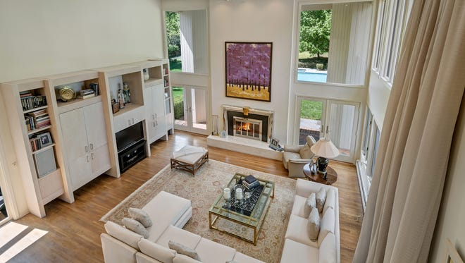 A two-story family room with built-ins, hardwood flooring, a fireplace, and expansive windows.