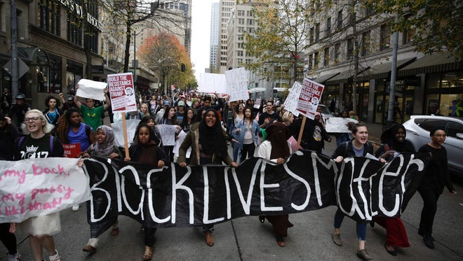 People carry a 'Black Lives Matter' banner during a student walkout protest against Trump in Seattle, Washington on November 14, 2016.