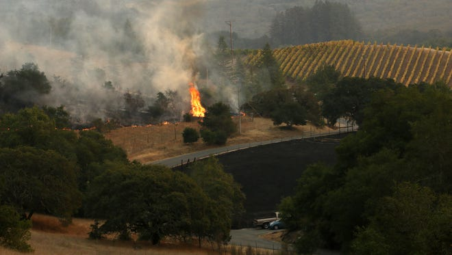 Flames are seen threatening a vineyard along Bennett Valley Road east of Santa Rosa, Calif. on Oct. 11, 2017. Jason Bean/Reno Gazette-Journal- USA TODAY NETWORK