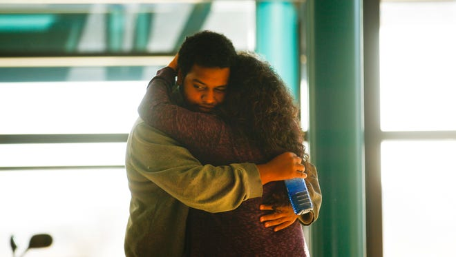 Aztec High School junior Canisius Phillips is reunited with his mother, Cindee Phillips, Thursday at her work place at the San Juan County Administration Building in Aztec.