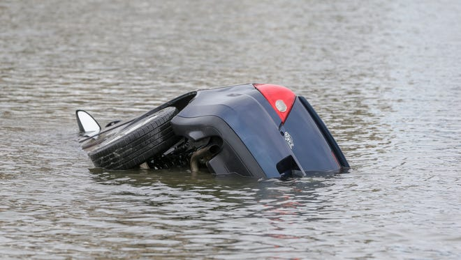 A car is pulled from a retention pond by members of the IFD Dive Rescue Tac Team 14 at the Core Riverbend Apartments in Indianapolis on Monday, March 26, 2018. A father drowned the previous evening while saving his young daughter from a car which rolled into a retention pond.