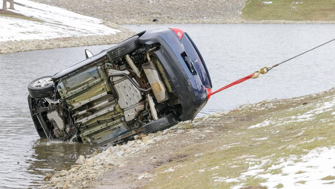 A car is pulled from a retention pond at the Core Riverbend Apartments in Indianapolis on Monday.