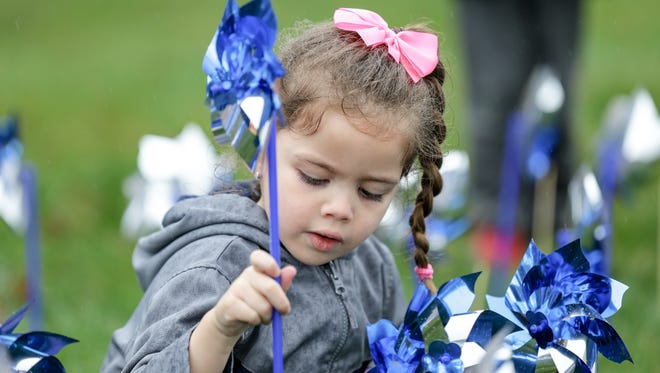 Emma Naggard helps to plant 1,000 pinwheels in front of The Villages Indiana and the Prevent Child Abuse Indiana headquarters in Indianapolis on Thursday, March 29, 2018. The Villages is just one of many nonprofits that have benefited from Lilly Endowment over the years.