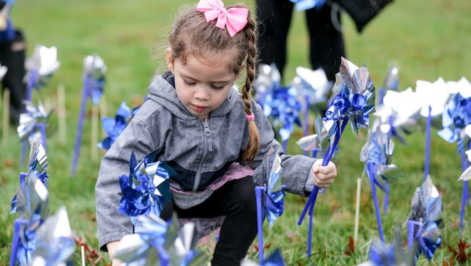 Volunteer Emma Naggard helps to plant 1,000 pinwheels in front of The Villages Indiana and the Prevent Child Abuse Indiana headquarters in Indianapolis on Thursday, March 29, 2018. The pinwheels are part of an initiative to raise funds and awareness to support child abuse prevention and education in Indiana during National Child Abuse Prevention Month.