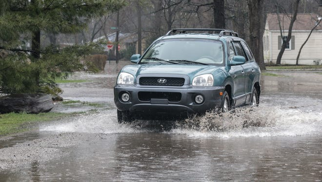 A car drives through the flooded intersection of Caroline and 67th St. during a morning of heavy rain and flash flooding in Indianapolis on Tuesday, April 3, 2018.