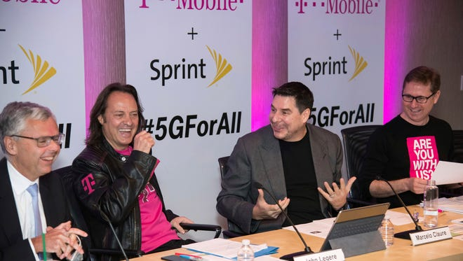 From left, Sprint President Michel Combes, T-Mobile CEO John Legere, Sprint CEO Marcelo Claure and T-Mobile President and COO Mike Sievert enjoy a laugh as they announce the merger of the two companies on April 29, 2018, in New York.