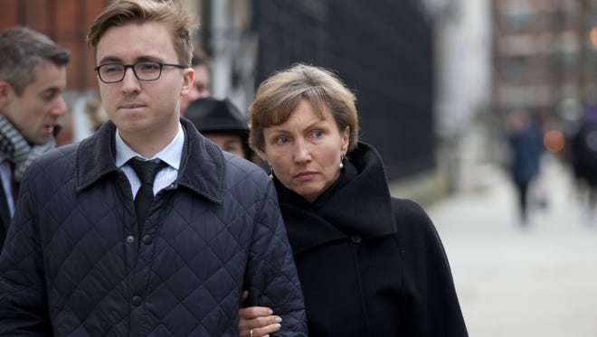 """Marina Litvinenko, the widow of former Russian intelligence officer Alexander Litvinenko, and their son Anatoly leave for the lunch break in proceedings at the Royal Courts of Justice in London, Tuesday, Jan. 27, 2015. A British judge opened an inquiry Tuesday into the death of Alexander Litvinenko, declaring the issues raised in the poisoning death of the former Russian intelligence agent to be of the """"utmost gravity."""""""