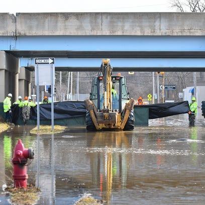 Work crews work to build a dam-like barrier, Thursday,