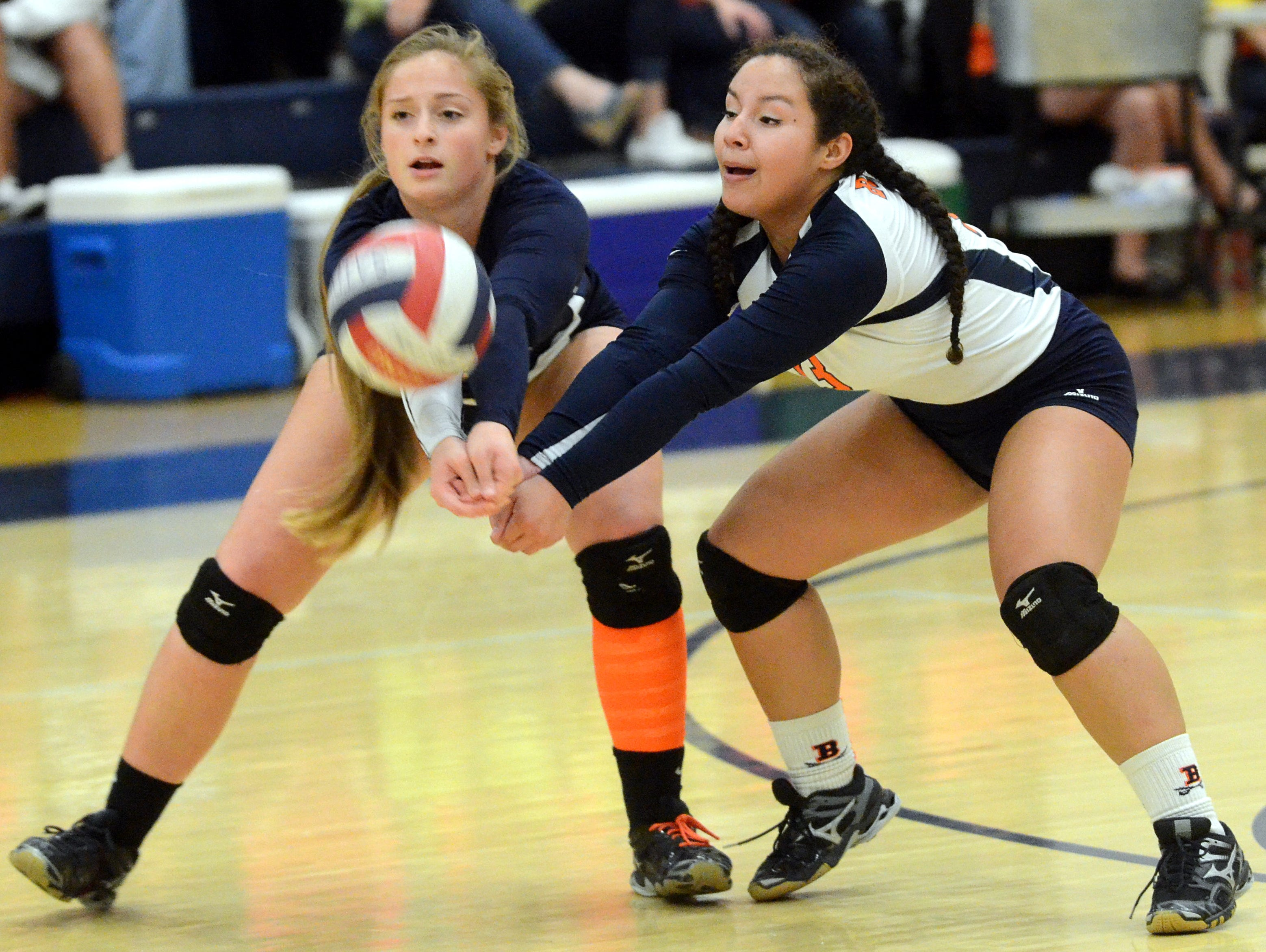 Beech High senior Saidee McDaniel and junior Veronica Gutierrez attempt to pass a serve during the first game of the Lady Buccaneers' sectional loss to Franklin on Thursday evening.
