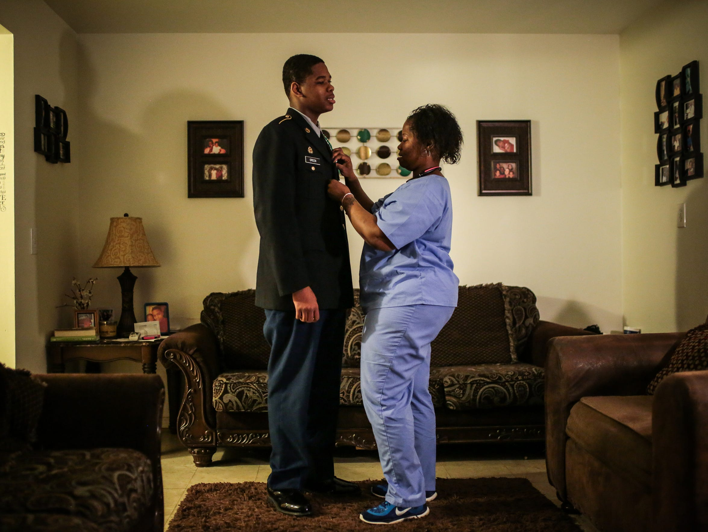 Quelyn Calhoun, 34, of Detroit, fixes the JROTC uniform