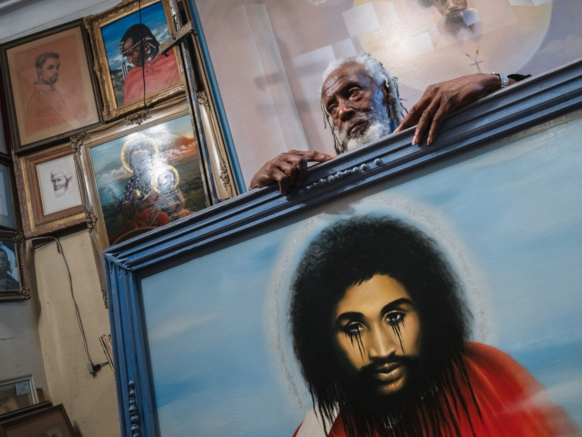 "Bennie White Jr. Ethiopia Israel of Detroit sits with a portrait of Malice Green he painted in his home in Detroit on Wednesday October 25, 2017. 'I didn't have any intention of painting his portrait,"" White Jr. Ethiopia Israel said of Malice Green who was beaten to death by Detroit Police Officers in 1992. The artist was inspired to paint a mural on an abandoned building that was defaced multiple times before being torn down after seeing the building that Green was killed in front of and his blood in the street with a little red rose as a token of love for him."