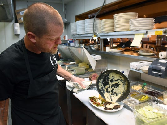 Chef Shaun Cayce prepares a Bifteki plate with green beans and potatoes at Mad Greek International Cafe. (MICHAEL PATRICK/NEWS SENTINEL)