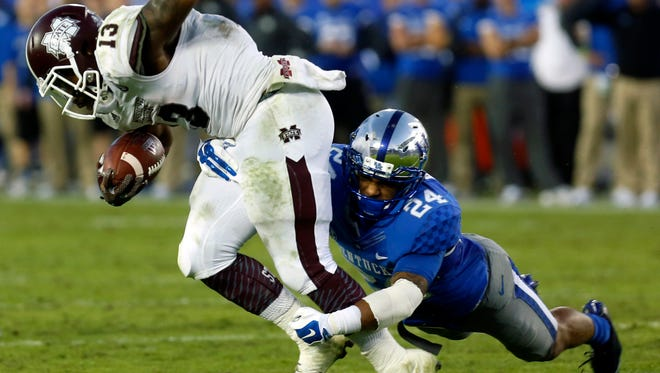Kentucky's  Blake McClain (#24) brings down Mississippi State's Josh Robinson behind the line of scrimmage.