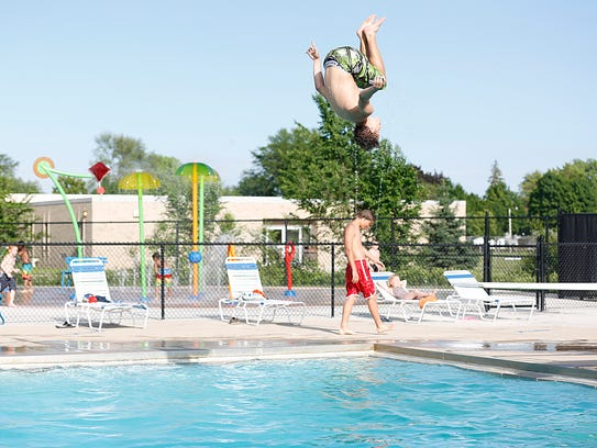 Cameron Hilt does a flip off the diving board Friday