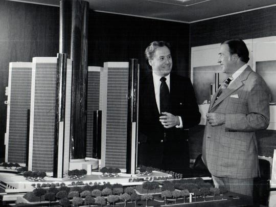 John Portman, left, architect for the Detroit riverfront development, shows Henry Ford II, board chairman of Ford Motor Company, an architectural model for the first phase of the development.