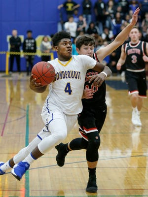 Irondequoit's Gerald Drumgoole dribbles the ball under pressure from Hilton's Colin Burkis in the first quarter at Irondequoit High School.
