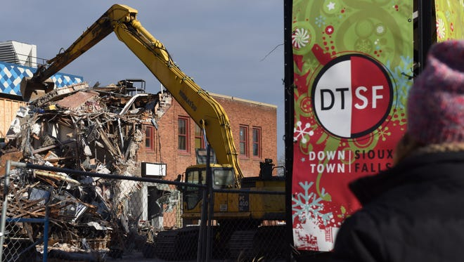 Onlookers watch on Thursday afternoon as the Copper Lounge building in downtown Sioux Falls is demolished from last week's collapse.