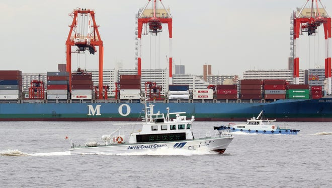 A Japan Coast Guard boat cruises in front of the international cargo terminal at Tokyo's port.
