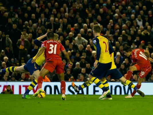 Liverpool's Philippe Coutinho, right, scores against Arsenal during the English Premier League soccer match between Liverpool and Arsenal at Anfield Stadium, Liverpool, England, Sunday Dec. 21, 2014. (AP Photo/Jon Super)