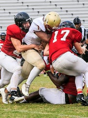 Stewarts Creek's Tayne Davis (17) helps on a tackle during Friday's scrimmage at Riverdale.