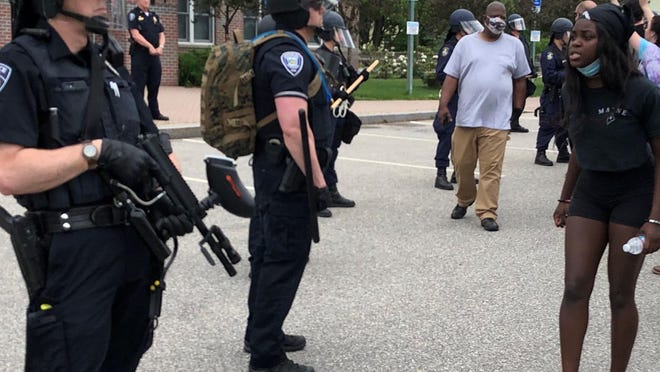 Hundreds marched to the Sanford Police Department headquarters on Saturday, where about two dozen officers stood silently with shields and weapons.