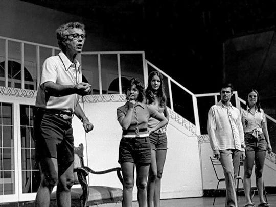 Dudley Birder, left, works with the cast on a Music