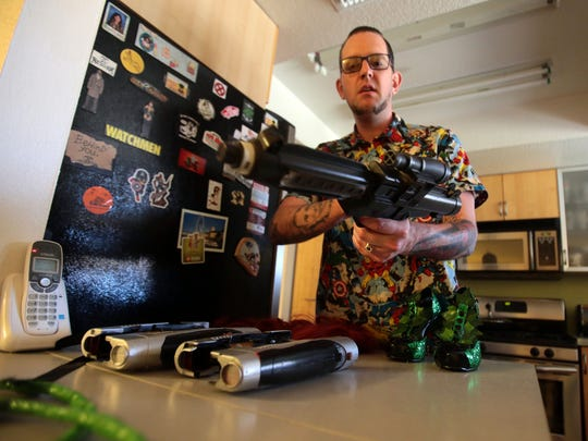 Andrew Whitney holds a prop gun for his Star Wars costume with two more prop guns for his Guardians of the Galaxy costume. Photo taken on July 20, 2016 in Indio.