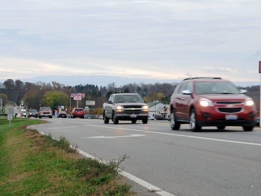People drive Friday on Western Avenue near Star Drive.