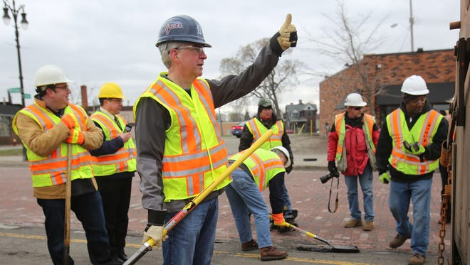 Gov. Rick Snyder gives the thumbs-up to a construction driver that he can move ahead as the governor assists MDOT workers along Michigan Avenue near Trumbull to patch potholes Thursday, April 23, 2015, in Detroit.
