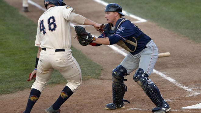 Kenosha's Jason Scholl is stopped at the plate by St. Cloud catcher Liam Bedford in the first game of the Northwoods League's Summer Collegiate World Series Thursday at Simmons Field in Kenosha, Wis.