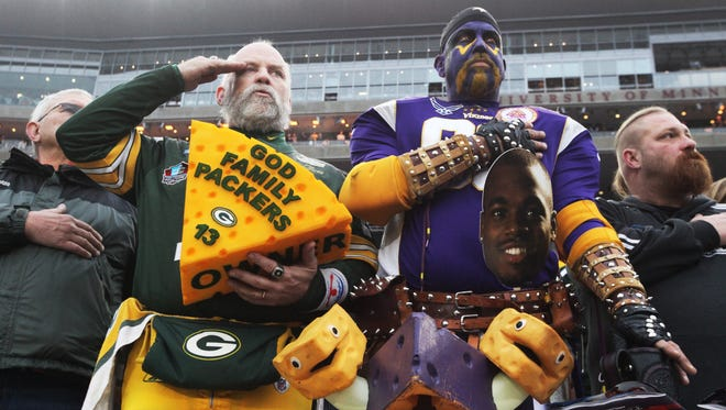 A Packers and Vikings fan pay their respects during the National Anthem before the Packers-Vikings game Nov. 23, 2014 at TCF Stadium in Minneapolis.