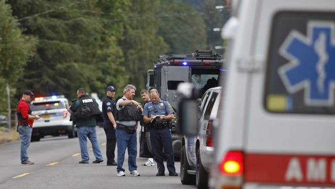 Law enforcement officers from several agencies investigate the scene of a shooting in Silverton on Saturday, Aug. 30, 2014.